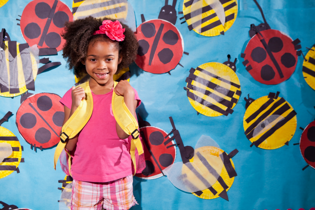Young girl with backpack in front of a school mural with ladybugs.