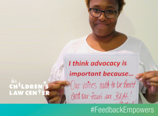 Advocate holding sign to promote the #FeedbackEmpowers campaign.