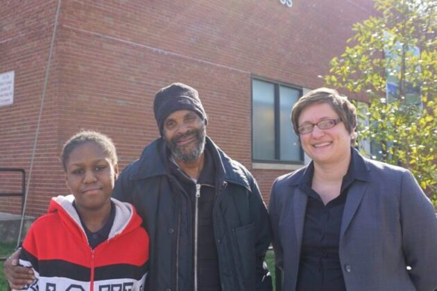 Photo of Destiny, her grandfather Tyrone, and their lawyer Rebecca outside Destiny's new school.