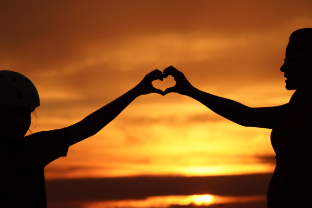Stock photo of people making a heart shape with their hands in front of a sunset.