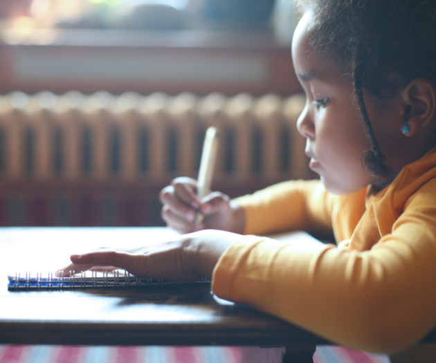 Young girl doing homework at a desk.