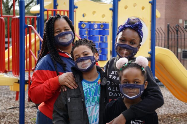 Family with masks at playground.