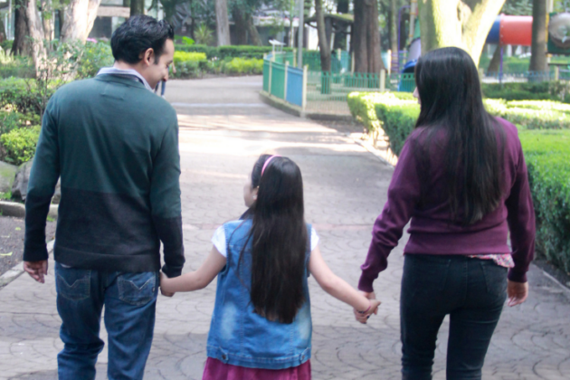 Family holding hands and walking in a part.