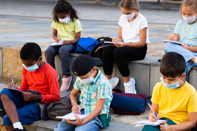 Kids wearing masks and studying outdoors.