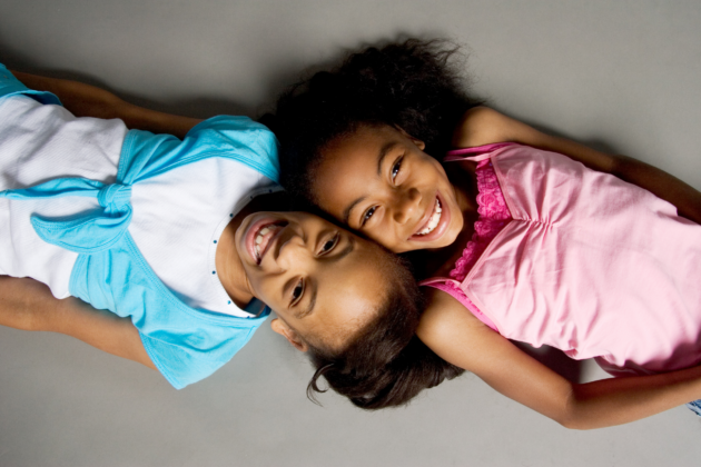 Stock photo of sisters smiling together.